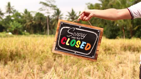 sorry : Man hands with closed sign board on a tropical nature background. Bali island.