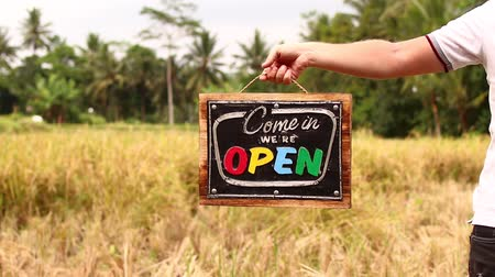 arduvaz : Open sign board in a man hands on a tropical nature background. Shooted on Bali island, full HD.
