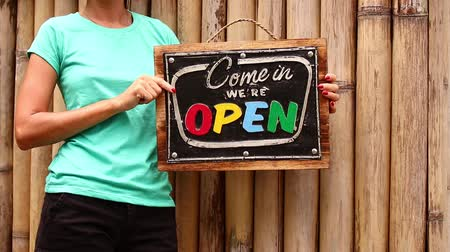 slate : Open sign board in a woman hands on a tropical nature background. Shooted on Bali island, full HD. Stock Footage