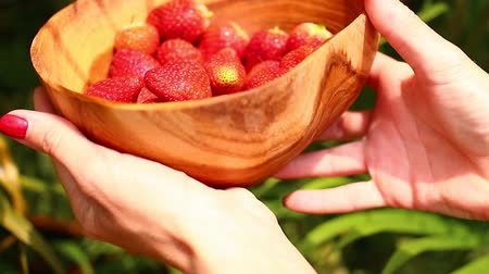 strawberries : Women hands with strawberry in a wooden bowl.