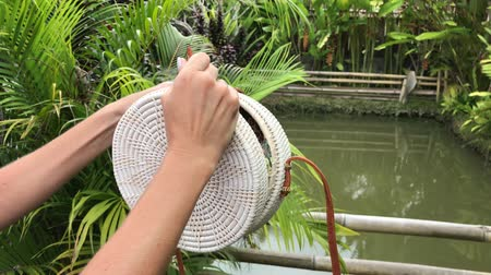 rotáng : Woman hands with stylich eco friendly rattan bag on a tropical background. Bali island.