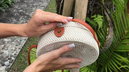 handbag : Woman hands with stylich eco friendly rattan bag on a tropical background. Bali island.