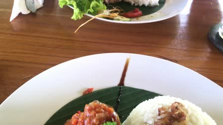 sea piece : Woman eating tuna bbq steak in a tropical cafe of Bali island, Indonesia.