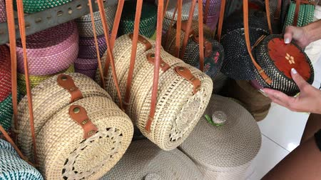 decisões : Woman choosing rattan eco bags in the art shop on Bali island, Indonesia. Woman stylish eco bag.