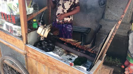 BALI, INDONESIA - FEBRUARY 21, 2019: Cooking sate ayam. Traditional indonesian street food, fried chicken.