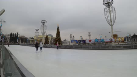 павильон : MOSCOW, RUSSIA - NOVEMBER 27, 2019: People riding on the big city ice skating rink at VDNKh.