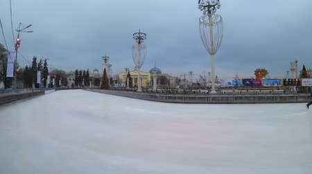 MOSCOW, RUSSIA - NOVEMBER 27, 2019: People riding on the big city ice skating rink at VDNKh. Hyperlapse. Stock mozgókép