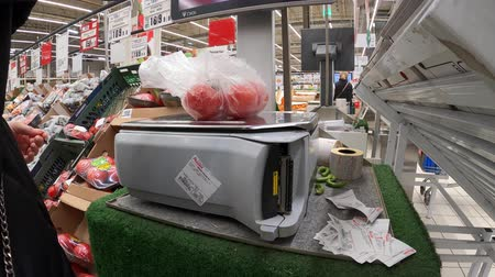 calcular : MOSCOW, RUSSIA - JANUARY 18, 2020: Supermarket, vegetable department. A woman weighs tomatoes.