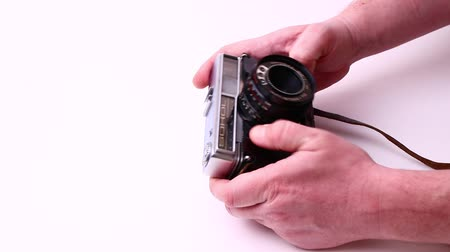 antikvitás : MOSCOW, RUSSIA - FEBRUARY 24, 2020: Vintage photo camera isolated on a white background. Men hands.