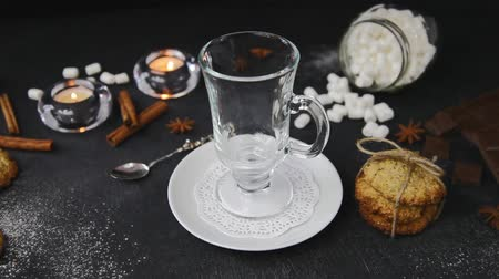 mályvacukor : Movie of pouring hot chocolate with marshmallows into glass. Beautiful background with candles, illicium, homemade cookies