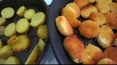 Papas caseras y nuggets de pollo fritos en una sartén Archivo de Video