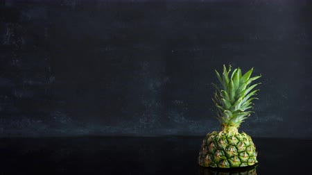 ananás : Stop motion ripe tropical fruit pineapple on a black background. Time lapse food loop footage