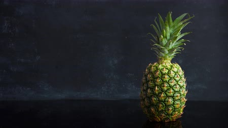 ananás : Stop motion ripe tropical fruit pineapple on a black background. Time lapse food footage