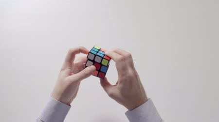 completo : Businessmans hands solving rubiks cube puzzle. Puzzle cube, puzzle game, best-selling toys. Mans hands in a shirt closeup. Rubiks cube is solved. Stock Footage