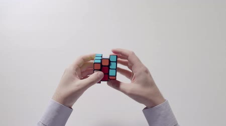 çözmek : Businessmans hands solving rubiks cube puzzle. Puzzle cube, puzzle game, best-selling toys.