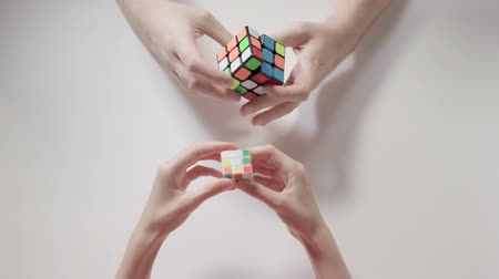 completo : Mans hands solving rubiks cube puzzle. Puzzle cube, puzzle game, best-selling toys.