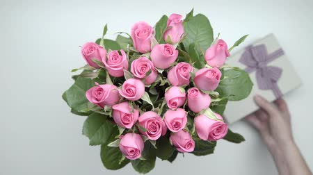darling : A bouquet of pink roses and presents on the table. 20