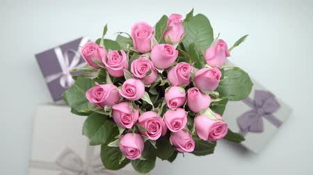 darling : A bouquet of pink roses and presents on the table. 24