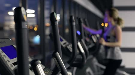 buty sportowe : view of emty gym with one girl on elliptical trainer working hard Wideo