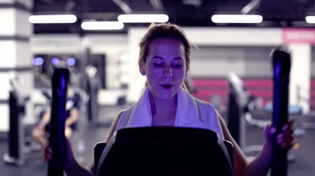 elliptical : Girl in gym on elliptical trainer in gym is working hard. blue colored Stock Footage