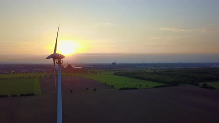 ambientalmente : Aerial footage of a wind turbine in front of the setting sun Wind Power - circling around wind turbine Stock Footage