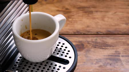 expressed : pour coffee maker with coffee in a white cup on a wooden table in the kitchen at the breakfast