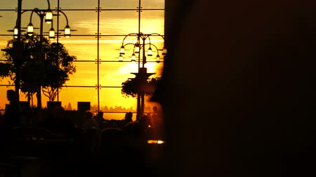 selektif : v13. A sequence of silhouette clips of airport travelers walking by and sitting at tables with sunset background.