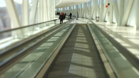 освещенный : v26. Airport travelers walking by while on moving walkway.
