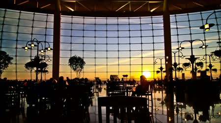 indústria : v8. Silhouette time lapse clip of airport travelers walking by and sitting at tables with sunset background and airplanes taking off. Stock Footage