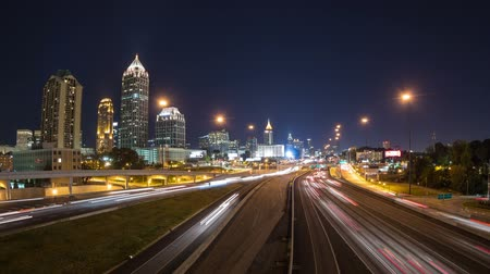 čas : v3. Zooming Atlanta cityscape time lapse over interstate freeway.