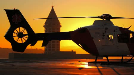 silhueta : v5. Medevac helicopter starting with beautiful backlit sunset. Vídeos