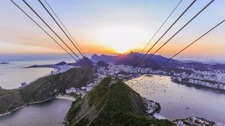 brazília : v10. Rio De Janeiro cityscape time lapse of sunset over Christ The Redeemer from Sugar Loaf Mountain.