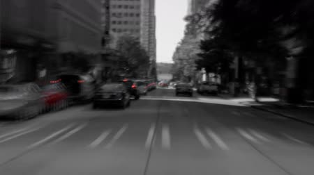 át : v1. Seattle city driving time lapse through downtown in black & white except red.