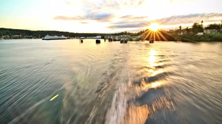feribot : v68. Rear view time lapse of ferry ride away from Bainbridge Island with a beautiful sunset. Stok Video
