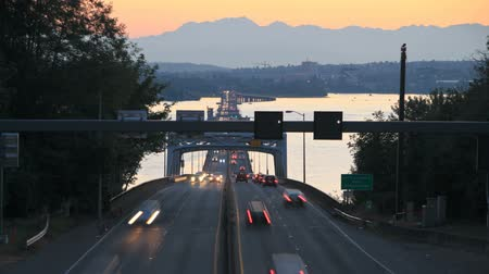 crowded : v1. Seattle highway 520 traffic time lapse right after sunset with cars coming and going over bridge part and Olympic Mountains in background.