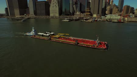 centrum : New York City Aerial v71 Flying low over East River panning up to reveal Manhattan Financial District cityscape and large barge. Dostupné videozáznamy