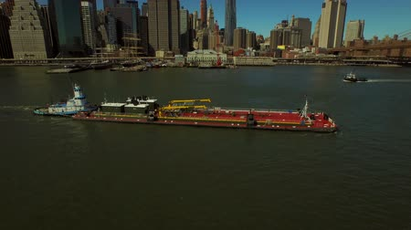 centrum : New York City Aerial v72 Flying low over East River panning up to reveal Manhattan Financial District cityscape and large barge.