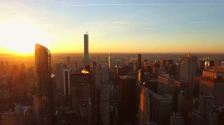 şafak : New York City Aerial v86 Flying low over Midtown Manhattan buildings towards beautiful sunrise.