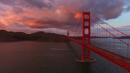 the suspension bridge : San Francisco Aerial v2 Flying low besides the Golden Gate Bridge at sunset. Stock Footage