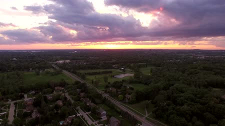 estrutura residencial : Troy Michigan Aerial v3 Flying low backwards over neighborhood with sunset views. Vídeos