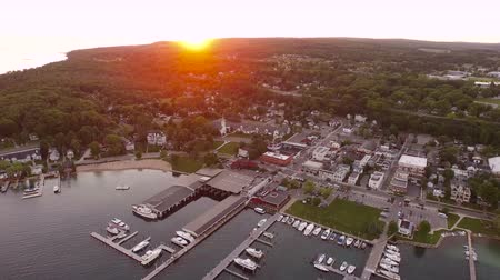 waterkant : Harbor Springs Aerial V4 vliegen achteruit over de stad in bij zonsondergang. Stockvideo