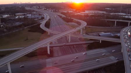construir : Atlanta Aerial v221 Flying low over Spaghetti Junction freeways panning up with cityscape sunset views.