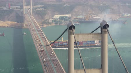 the suspension bridge : Hong Kong Aerial v35 Flying low around Tsing Ma Bridge with cargo ship passing by cineflex look. Stock Footage