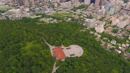 gözcü : Montreal Quebec Aerial v65 Birdseye flying over Mount Royal park panning up to cityscape Stok Video