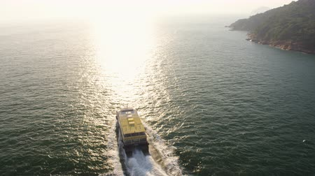 follow shot : Hong Kong Aerial v45 Flying low around small ferry headed to Macau at sunset.
