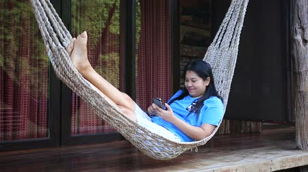 гамак : Asian woman relax on a hammock using smartphone