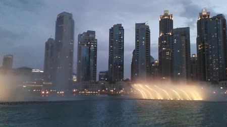largest city : Dubai, United Arab Emirates - May 1, 2013: Dubai Fountain show, world largest fountain on Burj Khalifa Lake, performs music show at sunset. On background, skyscrapers of Old Town Island at Dubai Mall. Stock Footage