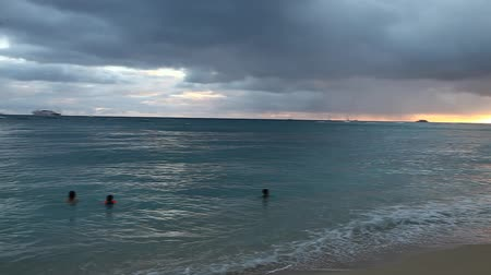 Оаху : Waikiki, Oahu, Hawaii - August 20, 2016: twilight at Waikiki beach. Waikiki beach is a beautiful place to enjoy the sunset over the ocean. People practice surfing paddling and swimming.
