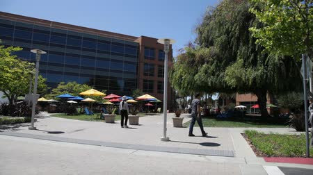 sobre : Mountain View, CA, USA - August 15, 2016: Google employees walking in relaxing area at Googles headquarters or Googleplex. Google is a multinational company specializing in Internet-related services.