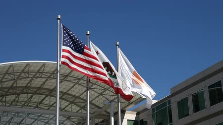 apple headquarter : Cupertino, California, USA - August 15, 2016: close up of flags in front of Apple Headquarters with American Flag and flag with Apple icon at One Infinite Loop in Cupertino, Silicon Valley.